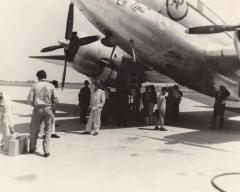 Passengers and crew outside a plane for migrant travel