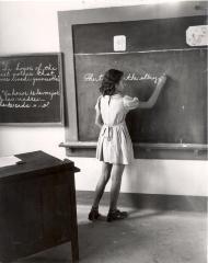 Elementary school student writing English sentences at blackboard