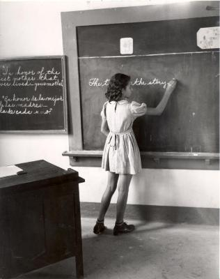 Elementary school student writing English sentences at blackboard