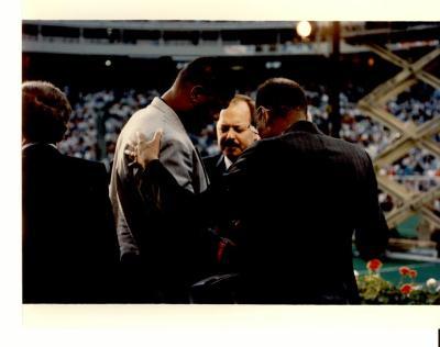 Reggie White, Nelson Diaz, and Rev. William B. Moore praying