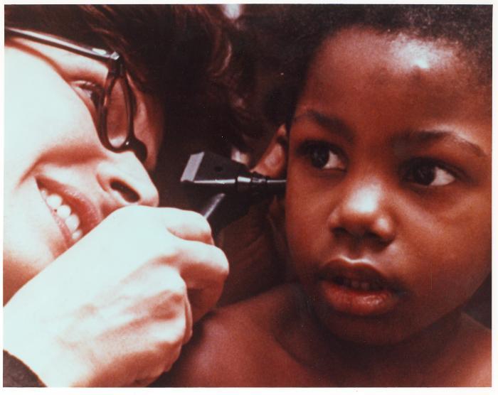 Helen Rodríguez-Trías doing an ear checkup on a child