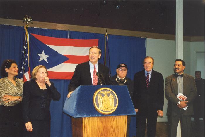 New York Governor George Pataki at podium, with Olga Méndez at left