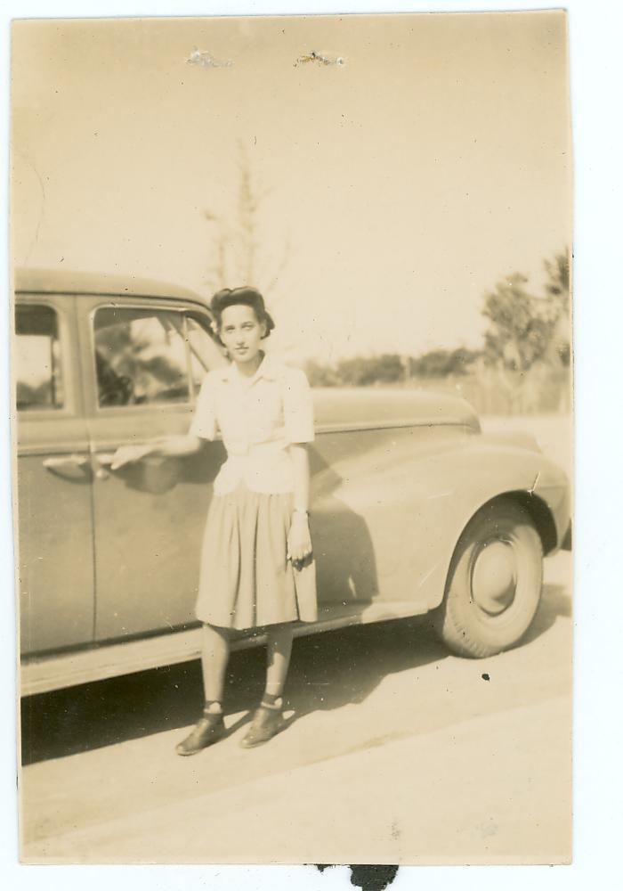 Young Antonia Pantoja standing in front of car