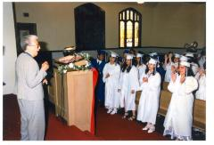 Students in white gowns during graduation