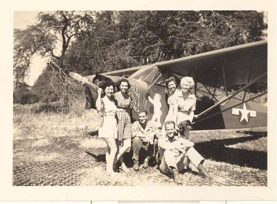 "Blase Camacho, friends, and two soldiers posing next to an airplane named ""Baby Butch"""