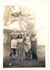 Blase Camacho, friend, and two soldiers wearing aprons near a beach