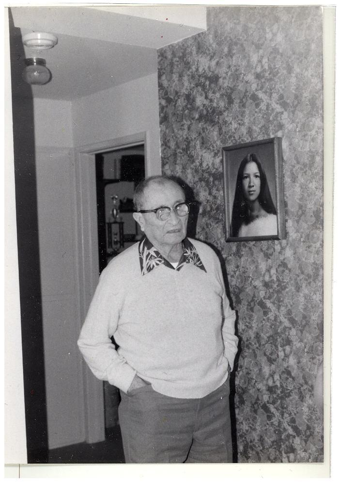 Lawrence Ramos Camacho next to a portrait