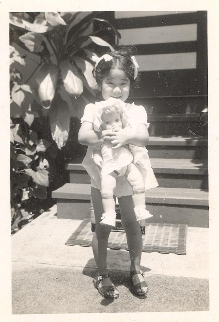 Linda Betsui smiling while holding a doll