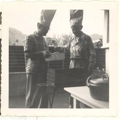 Two men wearing chef hats during Pat's christening