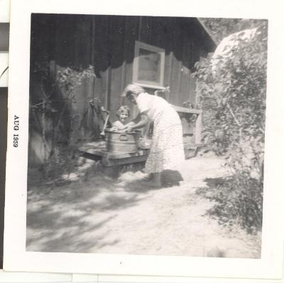Woman bathing child in a bucket