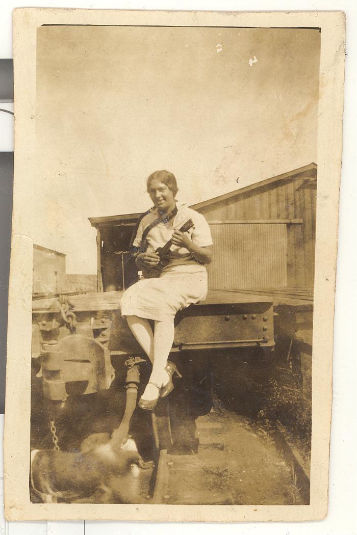 Mary Robello playing ukulele at train station