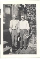 Two men posing in formal clothing in a Hawaiian sugar cane plantation