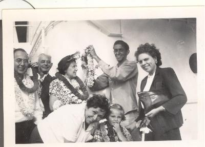 People smiling and wearing leis