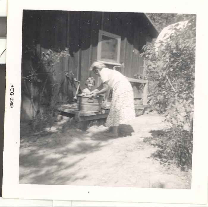 Woman bathing child in a bucket