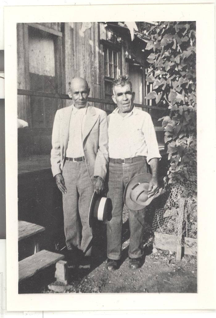 Two men posing in formal clothing in a Hawaiian sugar cane plantation