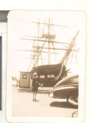 Woman in front of a large wooden ship