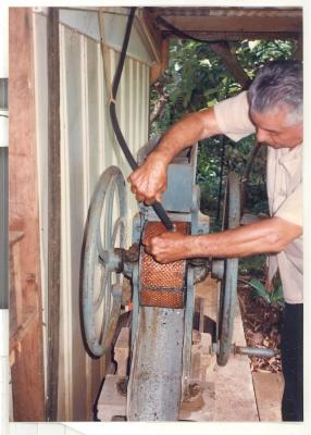 Man cleaning a sugar cane grinder with a hose