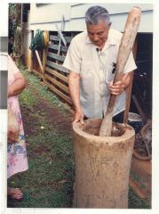 Man using giant wooden mortar and pestle