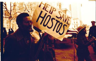 "Activist holding up a sign that reads ""Help Save Hostos"" during the Hostos Community College demonstrations"