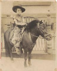 Olimpia Colón, six years old, in cowgirl outfit riding a pony