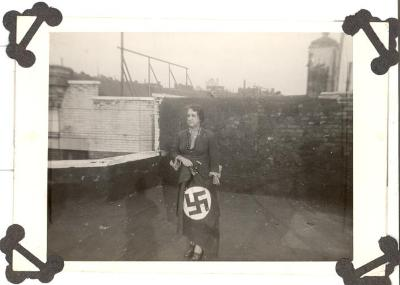 Elderly woman holding the Swastika flag during post-World War II period