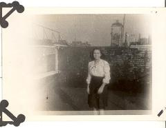 Young woman standing on rooftop in post-World War II period