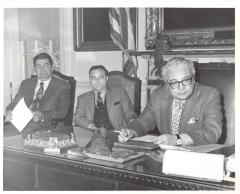 Joseph Monserrat (far right) at desk with two other men