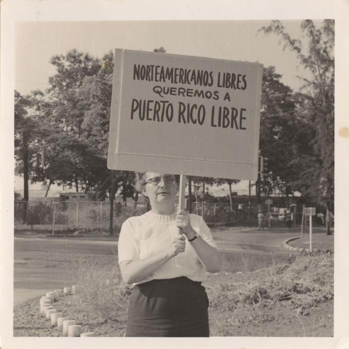 """Ruth Reynolds holding the sign, """"Norteamericanos libres queremos a Puerto Rico libre"""""""