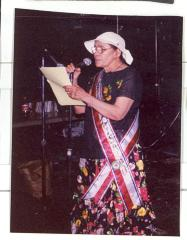 Woman in floral dress reading at the microphone