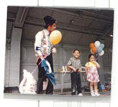 Clown performer with children and balloons