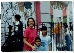 Woman with two young boys in front of a building with grattifi art