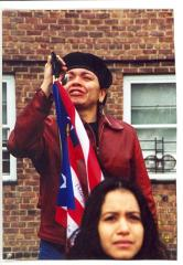 Woman in beret at microphone with Puerto Rican flag