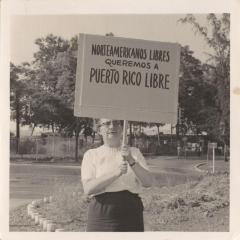 "Ruth Reynolds holding the sign, ""Norteamericanos libres queremos a Puerto Rico libre"""