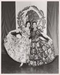 Two women wearing Mexican folkloric dresses