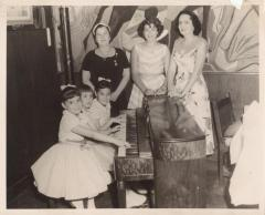 Three girls playing the piano, Genoveva de Arteaga and two women standing next to them