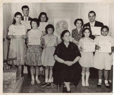 Genoveva de Arteaga with a group of young people holding a certificate