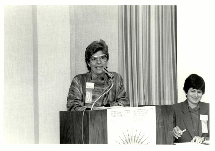 Helen Rodríguez-Trías speaking at podium on Hispanic Youth and Health