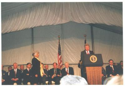 President Bill Clinton at podium with Helen Rodríguez-Trías at left