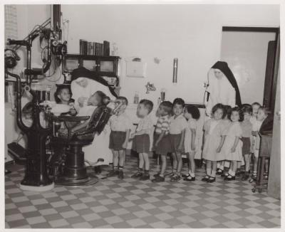 Nun performing a dental exam on a student