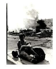 Boy on Big Wheels by Bronx building rubble