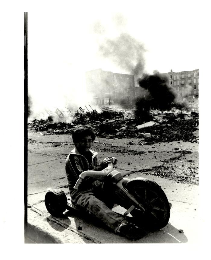 Boy on Big Wheels by Bronx building rubble