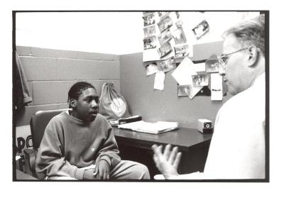 Boy speaking with mentor at the Police Athletic League