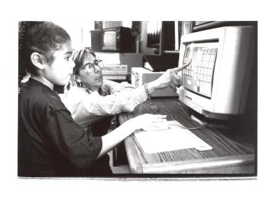 Computer instructor with child at the Police Athletic League