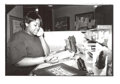Young woman answering phones at the Police Athletic League