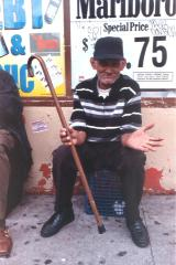 Elderly man with cane in front of bodega