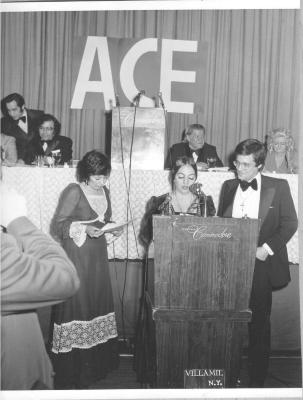 Gilda Mirós at left of podium during event